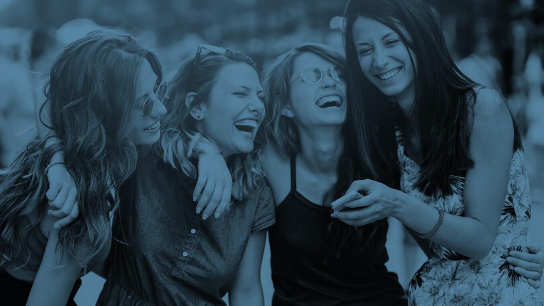 Jeunes femmes aux dents parfaites ayant eu un traitement Invisalign et souriantes entre amies